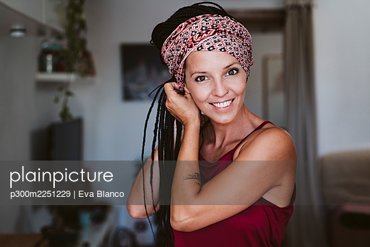 Woman wearing headscarf while standing at home - p300m2251229 by Eva Blanco