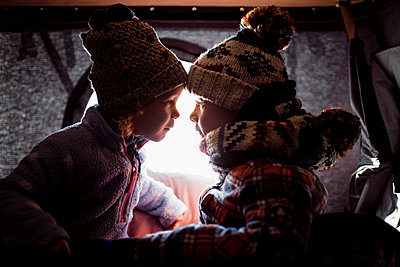 Siblings looking at each other while sitting in roof tent - p1166m1543202 by Cavan Images
