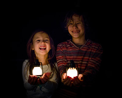 Two laughing children stand in shadows holding small lanterns in hands - p1166m2094457 by Cavan Images