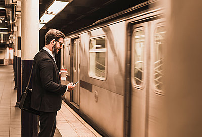 Young businessman waiting at metro station platform, using smart phone - p300m1191733 by Uwe Umstätter