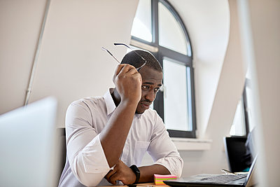 Worried male professional holding eyeglasses while looking at laptop in office - p300m2282740 by Zeljko Dangubic