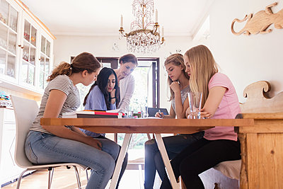 Mature woman assisting teenage girls in doing homework at home - p426m1196491 by Maskot