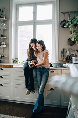 Full length of smiling female friends using mobile phone in kitchen at home - p426m1555876 by Maskot