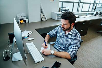 Caucasian businessman writing notes at a computer - p555m1503945 by FS Productions