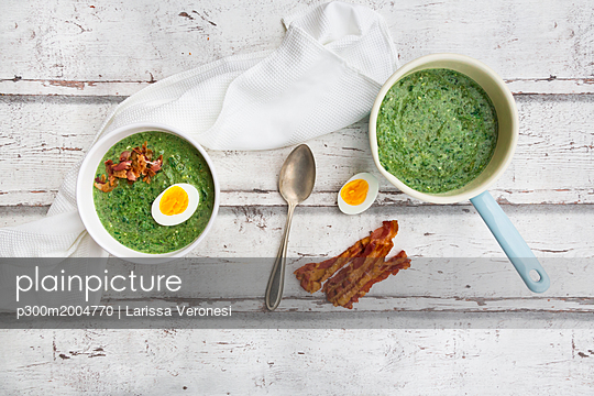 Spinach soup with egg and bacon - p300m2004770 von Larissa Veronesi
