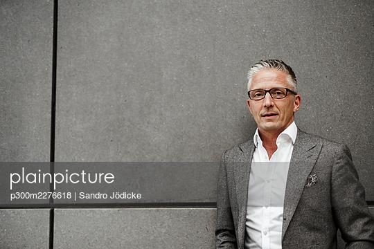 Male entrepreneur in gray blazer jacket against wall - p300m2276618 by Sandro Jödicke