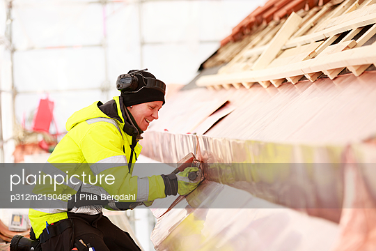 Woman working on roof - p312m2190468 by Phia Bergdahl