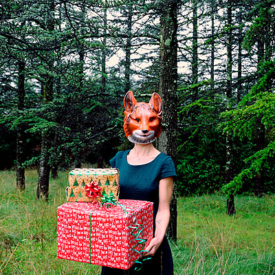 Woman with a fox mask holding gifts - p1521m2141331 by Charlotte Zobel