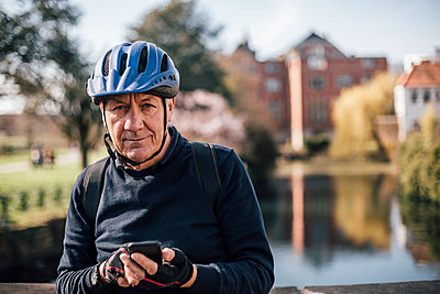 Portrait of senior man with cycling helmet using smartphone - p300m1581025 von Gustafsson