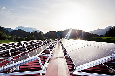 Austria, Tyrol, Koessen, back view of worker walking on solar plant in the evening - p300m1587168 by Christian Vorhofer