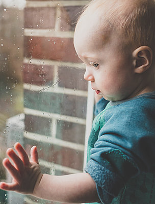 Baby girl looking through window covered with raindrops - p300m2120456 by Irina Heß