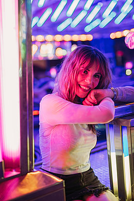 Portrait of a smiling young woman on a funfair at night - p300m2132309 by DREAMSTOCK1982