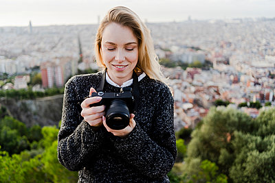 Young woman with camera above the city at sunrise, Barcelona, Spain - p300m2143995 by Giorgio Fochesato