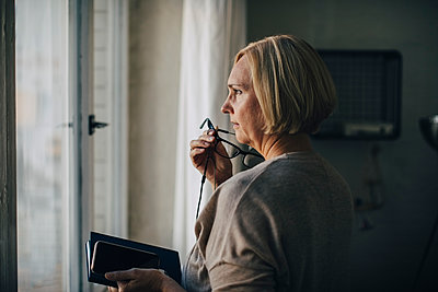 Mature businesswoman talking through earphones while standing by window in creative office - p426m2045973 by Maskot