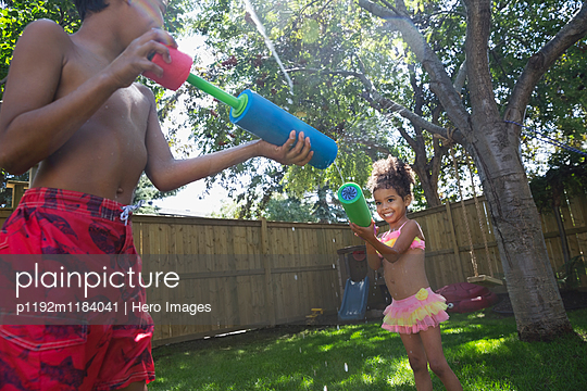 Playful brother and sister using squirt guns in backyard - p1192m1184041 by Hero Images