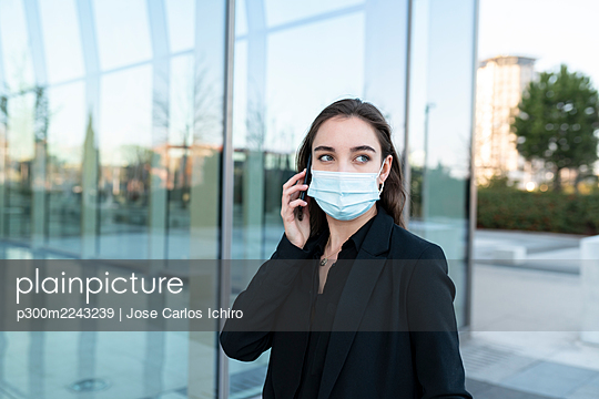 Young businesswoman wearing protective face mask talking on mobile phone while standing against building - p300m2243239 by Jose Carlos Ichiro