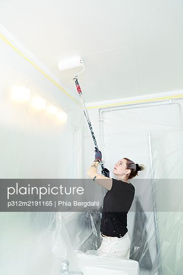 Woman painting ceiling - p312m2191165 by Phia Bergdahl