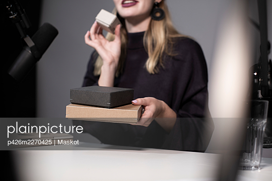 Midsection of businesswoman showing product while recording on camera - p426m2270425 by Maskot