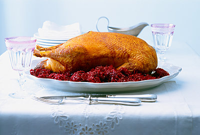 Crispy roasted goose with red cabbage on a festively laid table - p1053m2115328 by Joern Rynio
