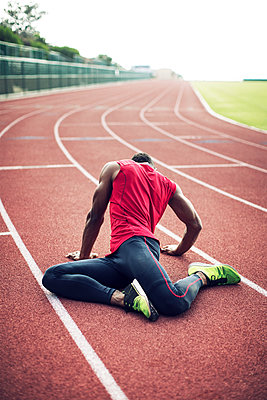 Male athlete stretching on running tracks - p1166m1088131f by John Trice