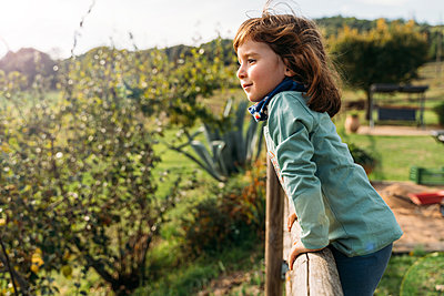 Portrait of smiling little girl leaning on wooden fence - p300m2143945 by Gemma Ferrando