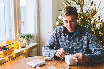 Finland, Man wrapping christmas gifts - p352m1350140 by Eija Huhtikorpi