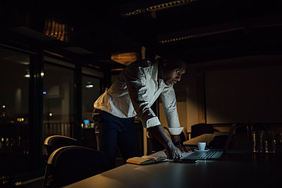 Young businessman in office at night looking at laptop - p429m2091531 by Eugenio Marongiu