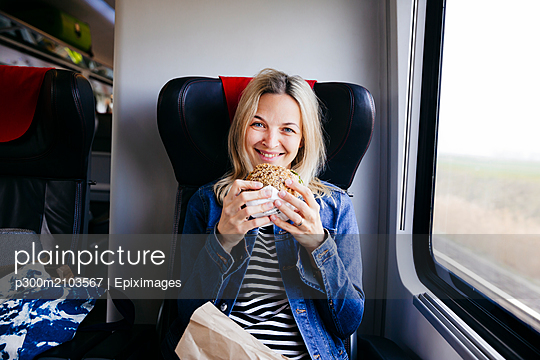 Portrait of smiling blond woman travelling by train having a snack - p300m2103567 by Epiximages