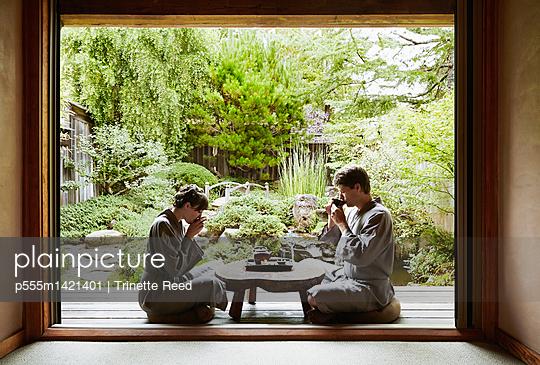 Caucasian couple in robes drinking tea in zen garden