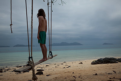 Man at beach stands on swing - p1324m1441284 by Michael Hopf