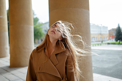 Young woman with windblown hair by columns - p1427m2169253 by Vyacheslav Chistyakov