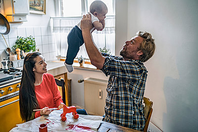 Family lifting up baby at kitchen table at home - p300m2132446 by Richárd Bellevue
