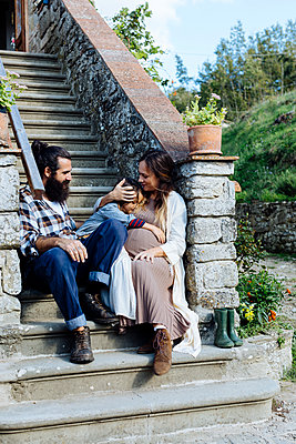 Family relaxing on stoop of a rustic house - p300m2144427 by Sofie Delauw