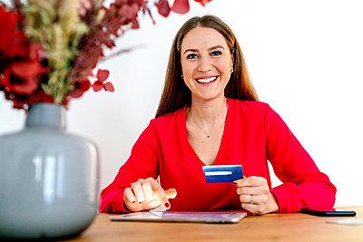 Smiling beautiful woman making card payment through digital tablet at table - p300m2277084 by Oxana Guryanova