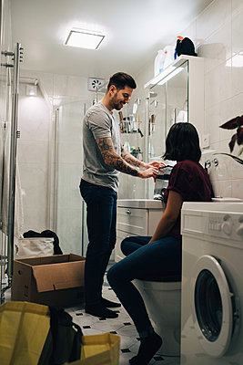 Man and woman unpacking in bathroom at new home - p426m1542772 by Maskot