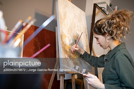 Young woman painting in her atelier - p300m2079872 by Jorge Garcia-Romeu Senante