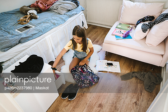 Caucasian girl packing bag in bedroom at home - p426m2237980 by Maskot