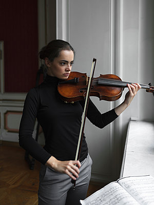Confident woman with sheet music on window sill playing violin while standing in mansion - p1166m2011262 by Cavan Images