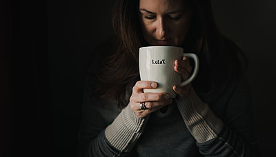 Woman drinking from large coffee mug with word relax written on it. - p1166m2095441 by Cavan Images