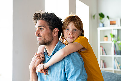 Daughter with blue eyes embracing father in living room - p300m2267320 by Steve Brookland