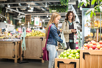 Mother and daughter buying apples in supermarket - p426m1407406 by Kentaroo Tryman