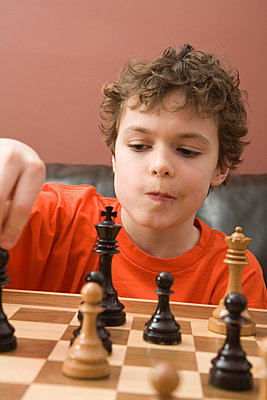 Boy playing chess - p4342494f by Marv Johnson
