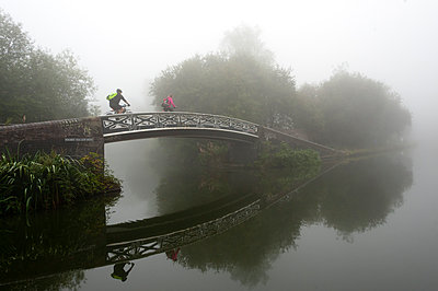 A cyclist on a bridge on Birmingham Canal Navigations , Birmingham, West Midlands, England, United Kingdom, Europe - p871m1206570 by Graham Lawrence