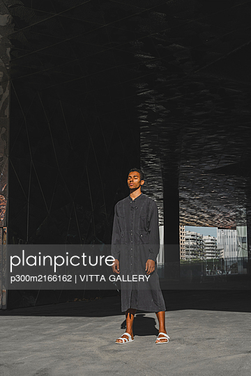 Young man wearing black kaftan standing outdoors - p300m2166162 von VITTA GALLERY