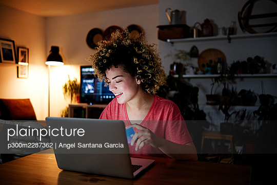 Smiling young woman sitting with laptop and credit card at home - p300m2287362 by Angel Santana Garcia