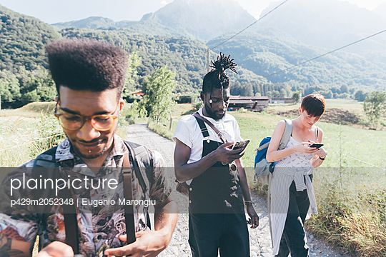 Young adult hikers on rural dirt track looking at smartphones,  Primaluna, Trentino-Alto Adige, Italy - p429m2052348 by Eugenio Marongiu