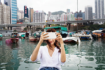 Female tourist photographing at harbor in city - p1166m1150886 by Cavan Images