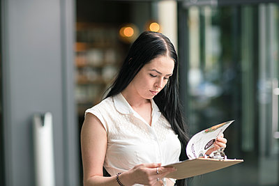 Young businesswoman holding a check list - p1332m1540007 by Tamboly