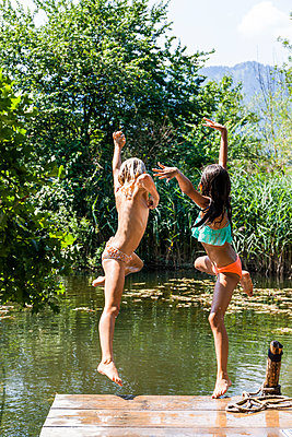 Two carefree girls jumping into pond - p300m2030371 von Tom Chance
