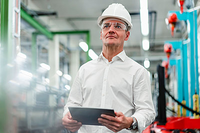 Mature businessman in hardhat holding digital tablet while looking away in factory - p300m2242271 by Daniel Ingold